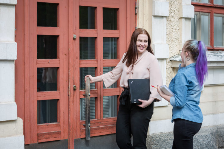 Kaksi opiskelijanuorta katsoo toisiin hymyillen ja toinen avaa kansanopiston oven.