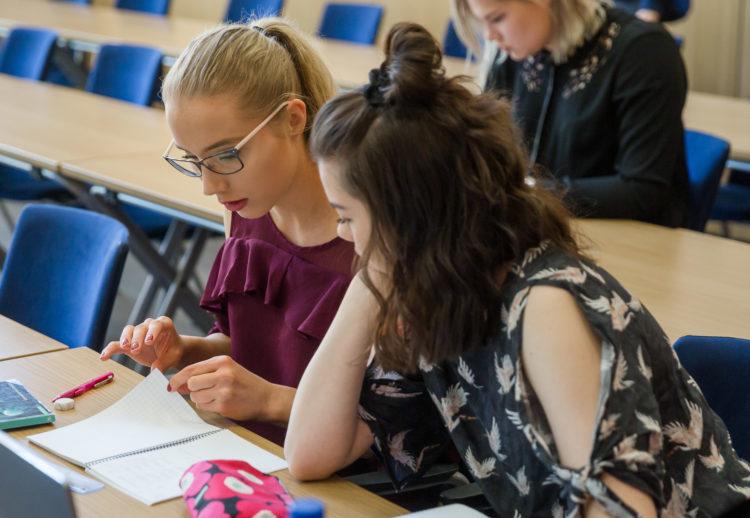 Kaksi tyttöä opiskelee luokkahuoneessa.